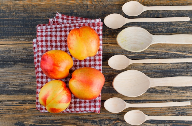 Nectarines with wooden spoons flat lay on wooden and kitchen towel Free Photo