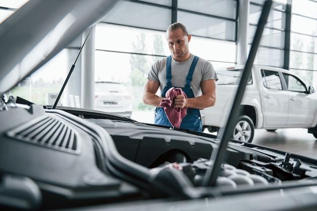 Нужно присмотреться. мужчина в синей форме работает с разбитой машиной. ремонт Бесплатные Фотографии