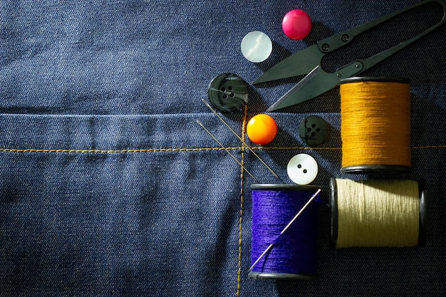 Needle and threads against plastic button and thread cutting scissors on jeans fabric. Premium Photo