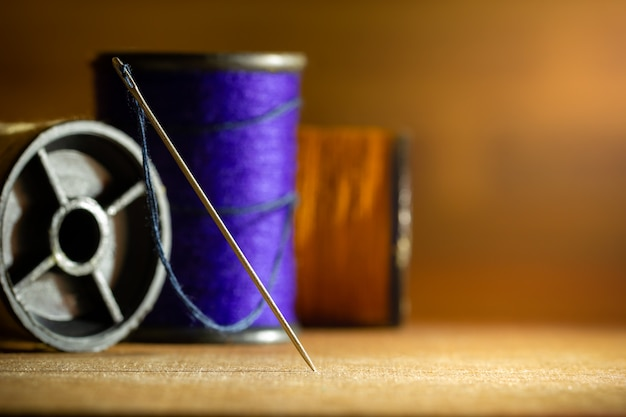 Needle and threads on wooden table. Premium Photo