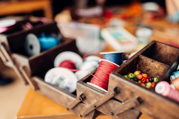 Рукоделие, шкатулка с разноцветными веревками, бусами и аксессуарами на деревянном столе, никто. ремесленные инструменты. модный декор ручной работы Premium Фотографии