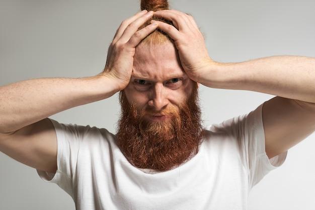 Отрицательные человеческие эмоции, чувства, реакция и отношение. портрет напряженного разочарованного молодого небритого мужчины, сжимающего голову, раздраженного шумом, страдающего от головной боли, имеющего болезненный вид Бесплатные Фотографии