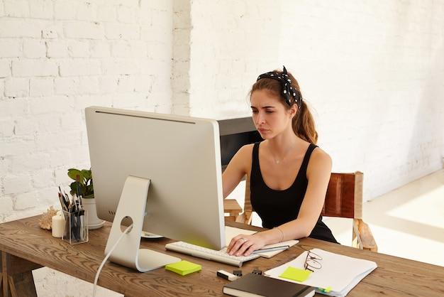 Emozioni umane negative. la donna sconvolta guarda lo schermo che lavora alla scrivania davanti al computer in un ufficio moderno. stanco designer o architetto che lavora alla scrivania Foto Gratuite