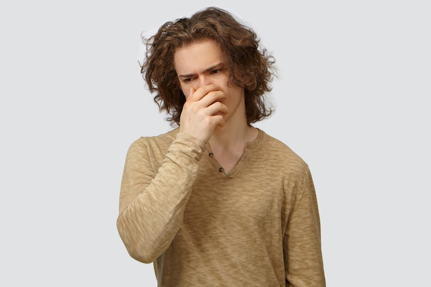 Negative human expressions, feelings and reaction. picture of fashionable guy with wavy hair going to throw up, covering mouth with hand to suppress vomit because of disgusting smell or rotten food Free Photo