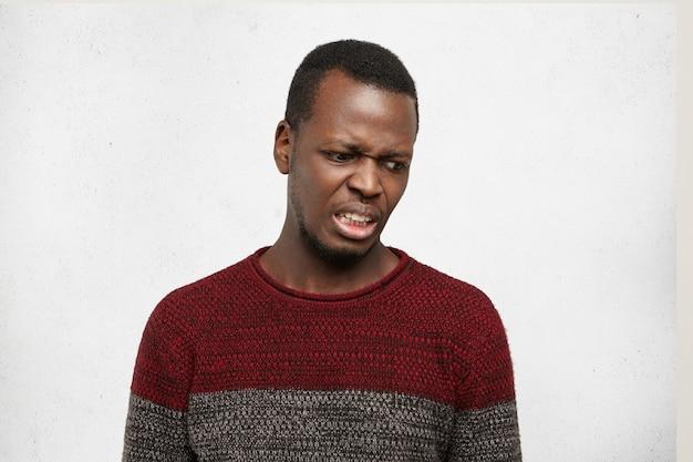 Espressioni facciali, emozioni e sentimenti umani negativi. ritratto di schifoso disgustato giovane maschio afroamericano che guarda terrorizzato e disprezzo, provando odio e disgusto verso qualcosa Foto Gratuite