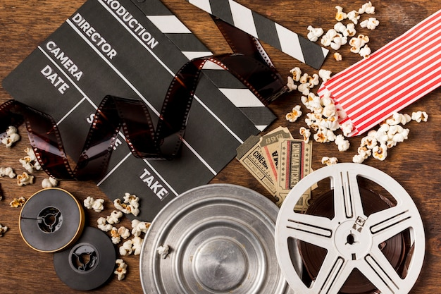 Negatives stripes with clapperboard; film reels; tickets and popcorn on wooden desk Free Photo