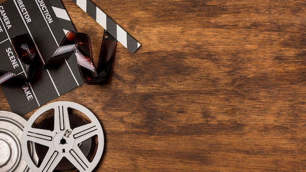 Negatives stripes with clapperboard and film reels on wooden desk Free Photo