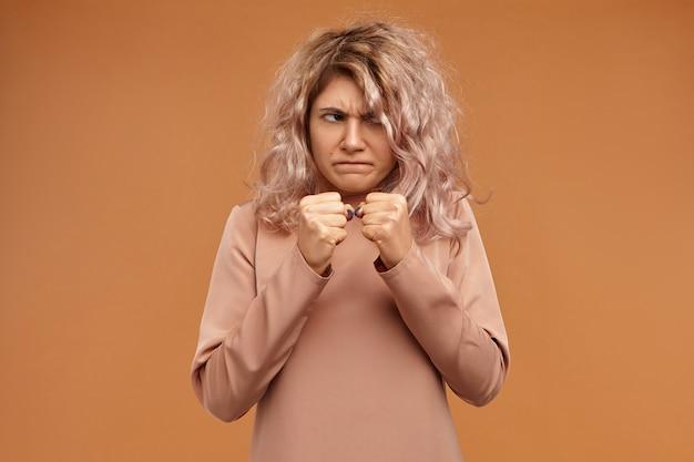 Concetto di negatività, aggressività e rabbia. giovane donna caucasica emotiva divertente che aggrotta le sopracciglia, tenendo i pugni chiusi davanti a lei, pronta a prendere a pugni il nemico Foto Gratuite