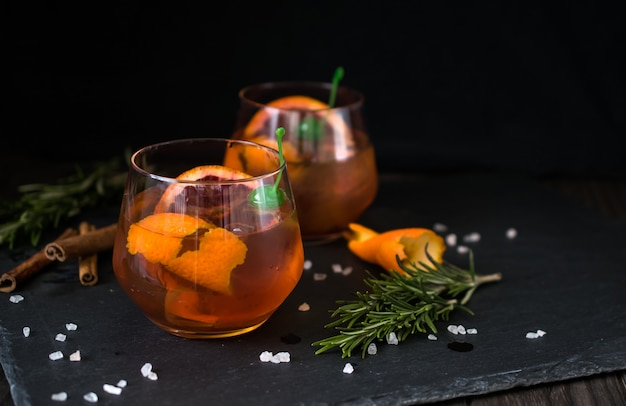 Negroni cocktail on black served with a slice of orange and rosemary. Premium Photo