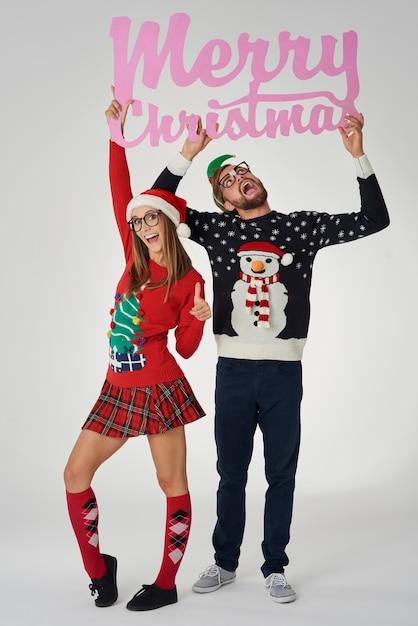 「メリークリスマス」とテキストを保持しているオタクカップル 無料写真