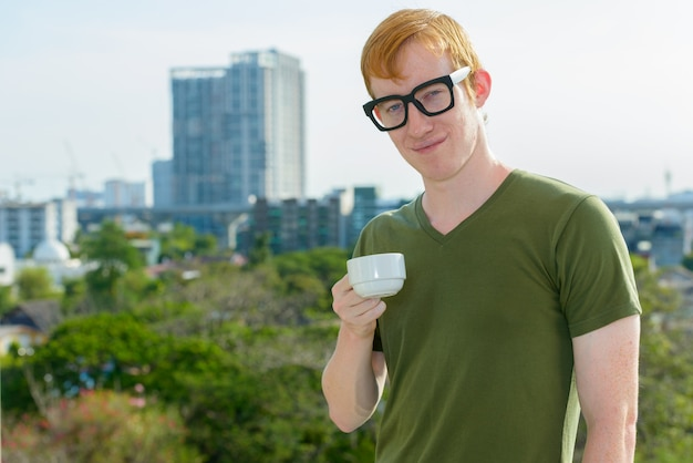 Ботаник с рыжими волосами пьет кофе на фоне города Premium Фотографии