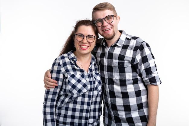 オタク、オタク、眼鏡をかけた、面白い人々の概念-眼鏡をかけた面白いカップルが白を抱いています Premium写真
