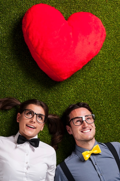 Nerdy couple in love lying down on grass Free Photo
