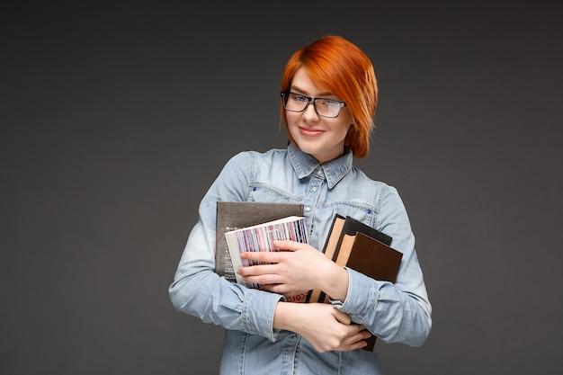 Всезнайка рыжая студентка несет книги Бесплатные Фотографии