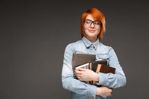 Nerdy redhead female student carry books Free Photo