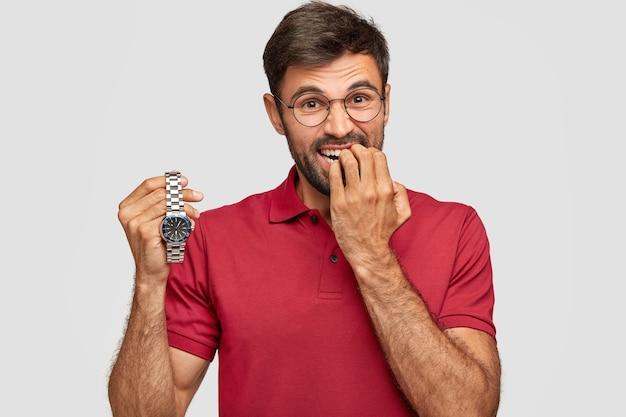 神経質なひげを生やした男性が指の爪を噛み、腕時計を持ち、重要な会議に遅れるのではないかと心配し、カジュアルなtシャツを着ています。恥ずかしい青年が何かを待っています。時間はすぐに飛ぶ 無料写真