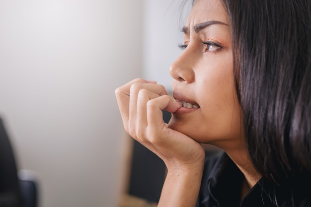 Nervous businesswoman biting her nails with worry emotion in office. Premium Photo