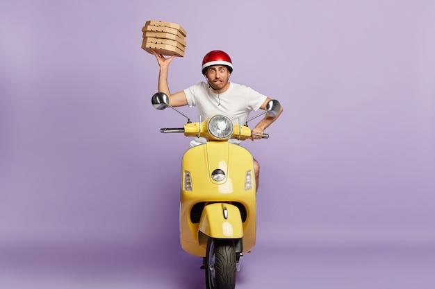 Fattorino nervoso alla guida di scooter mentre si tengono scatole per pizza Foto Gratuite