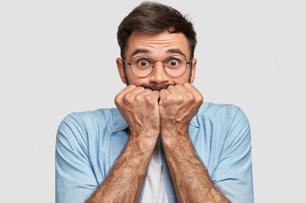 Il maschio spaventato nervoso tiene i pugni vicino alla bocca, ha un'espressione preoccupata, fissa, isolato sopra il muro bianco. un giovane uomo con la barba lunga si sente depresso. persone e concetto di preoccupazione Foto Gratuite