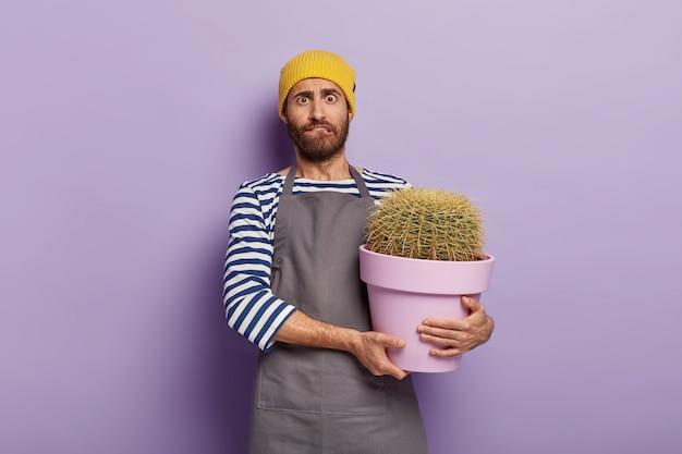 Giardiniere nervoso in posa con un grande cactus in vaso Foto Gratuite