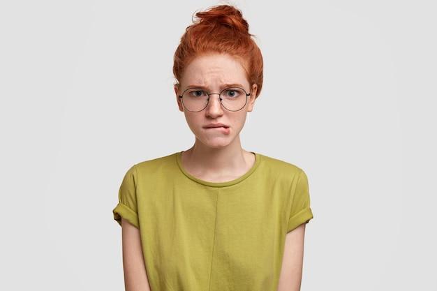 神経質な生姜の女性が唇を噛み、不満の表情を持ち、何かに疑問を持ち、カジュアルなtシャツを着ています 無料写真