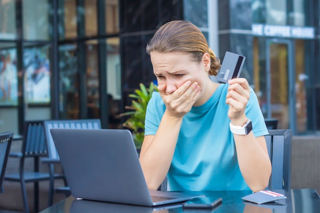 Nervous horrified confused young woman, stressed worried lady having problem with paying, buying online, payments with credit blocked bank card, looking at screen, monitor of laptop. internet fraud Premium Photo