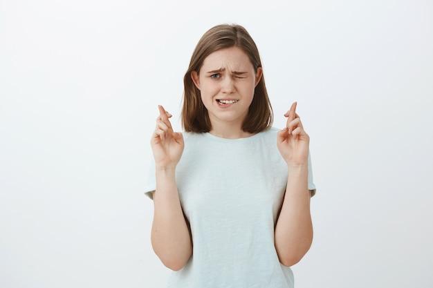 Figlia nervosa insicura incrocia le dita per avere fortuna sbirciare con un occhio la tabella dei risultati mentre aspetta i voti essere ansiosa e preoccupata pregare perché i desideri si avverino Foto Gratuite