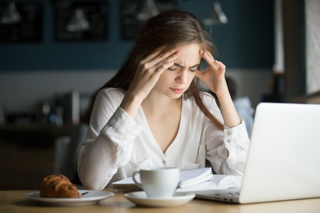 Nervous stressed female student feeling headache studying in cafe Free Photo