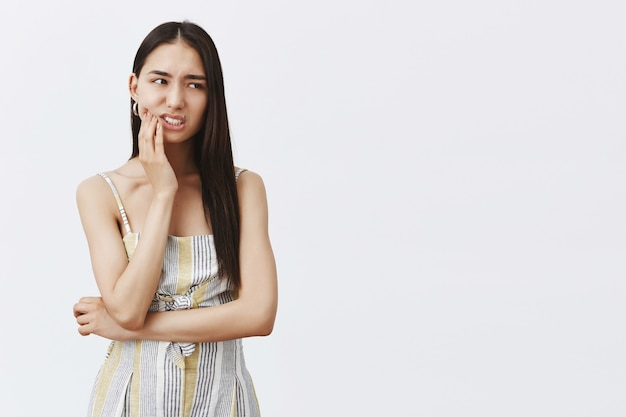 Nervous troubled attractive and fashionable female model in matching outfit, holding palm on jaw, staring right anxiously Free Photo