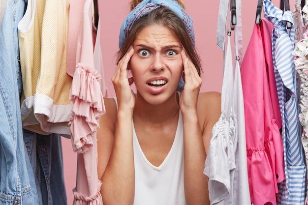 洋服のワードローブの近くに立っているときに恐ろしそうに顔を見つめ続けている緊張の女性。彼女は友人との会議のために着るものがないことに気づきました。否定的な人間の感情の概念 無料写真