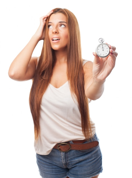 Nervous woman with long hair holding stopwatch Free Photo