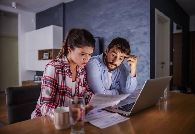 Нервная молодая пара, сидя дома, оплачивая счета в интернете. Premium Фотографии