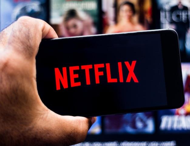 Netflixロゴを表示しているandroidモバイルデバイスを抱きかかえた。 Premium写真