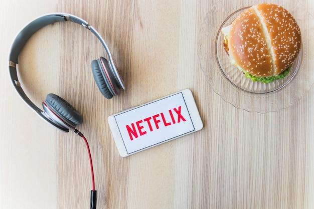Netflixロゴ近くのヘッドフォンとハンバーガー 無料写真