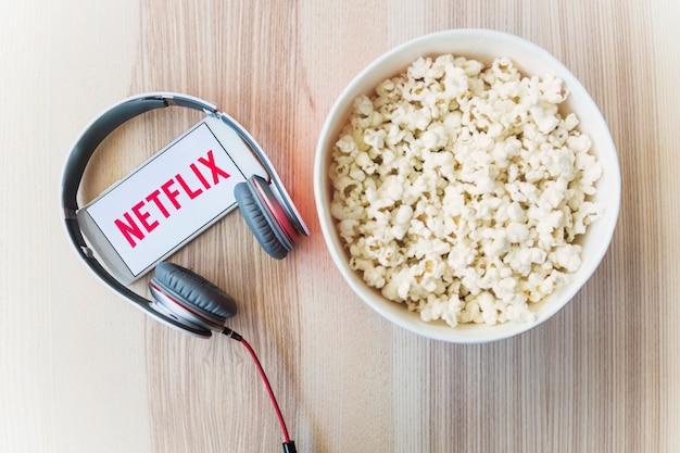 Netflixロゴ付きのスマートフォンに近いヘッドフォンとポップコーン 無料写真