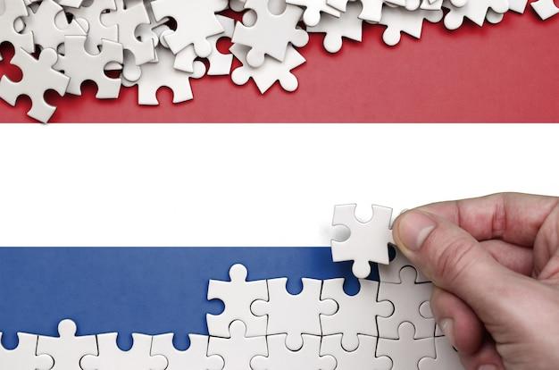 オランダの旗は、人間の手が白い色のパズルを折るテーブルに描かれています Premium写真