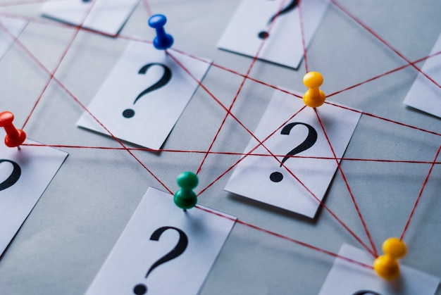 Network of printed question marks on white cards Premium Photo