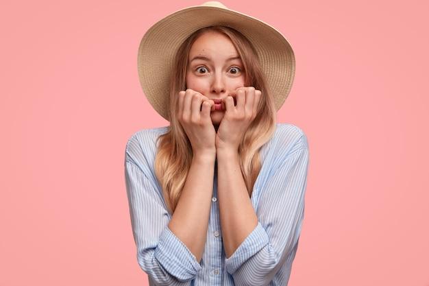 帽子とシャツを着た神経症の美しい女性は、指の爪を噛み、恐怖で見つめ、ピンクの壁に隔離された何かに不安を感じます。上品な若い女性は神経質に見えます。人と気持ち 無料写真