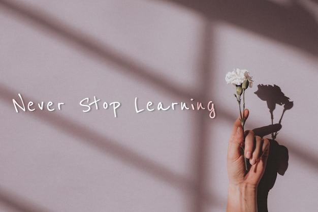 Non smettere mai di imparare la citazione e la mano che tiene il fiore Foto Gratuite