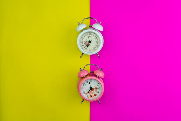 New alarm clock on pink and yellow paper pastel color background Premium Photo