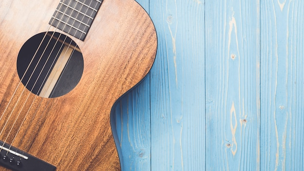 New brown guitar on wooden board Premium Photo