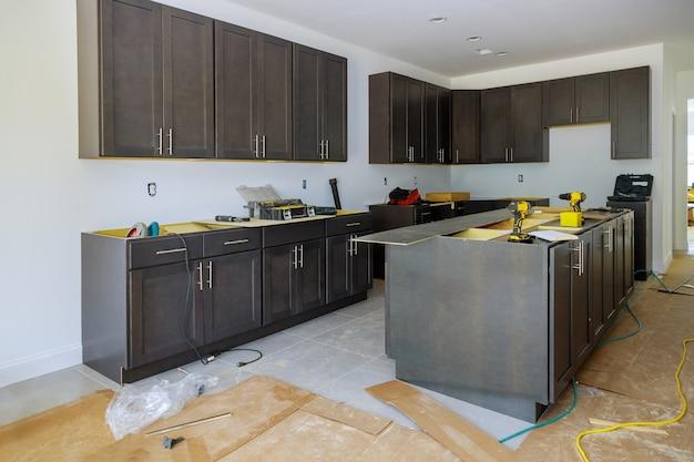 設置ベースの家具のインストールされたホームセンターのキッチンビューの新しいキャビネットは、キャビネットの引き出しです。 Premium写真