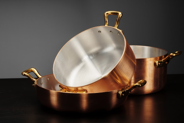 New copper cooking ware over dark Premium Photo