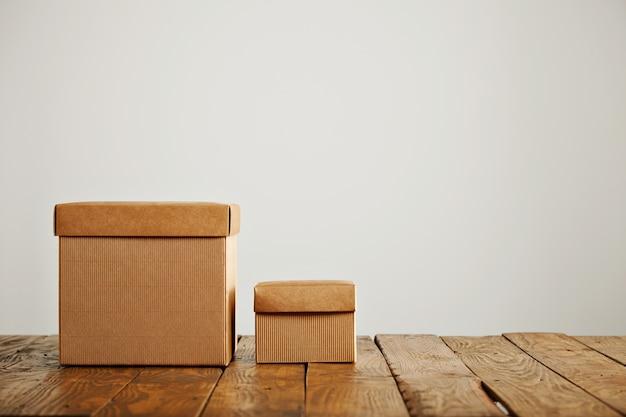 흰 벽이있는 스튜디오에서 오래된 거친 나무 테이블과 대조되는 커버가있는 새로운 크기의 베이지 색 골판지 상자 무료 사진