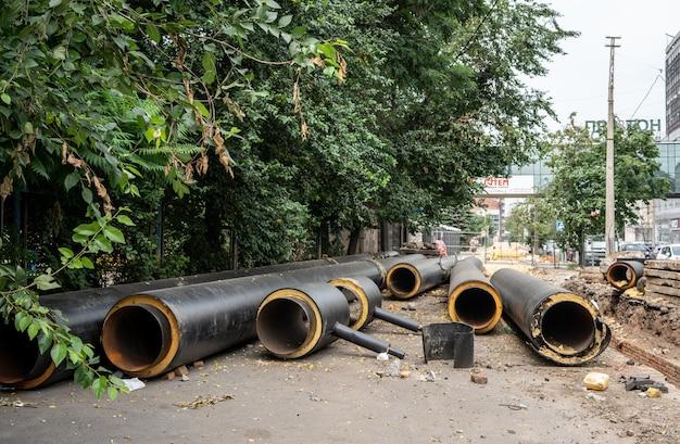緑の木々の近くの夏の日に屋外に横たわっている新しい断熱された黒い水道管 Premium写真