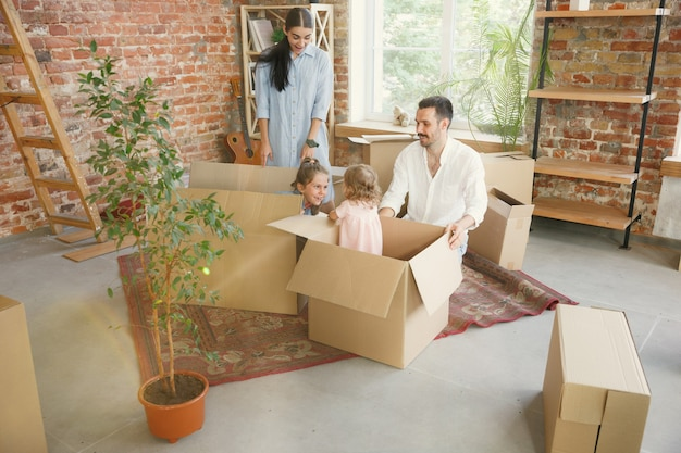 New life. adult family moved to a new house or apartment. spouses and children look happy and confident. moving, relations, new life concept. unpacking boxes with their things, playing together. Free Photo