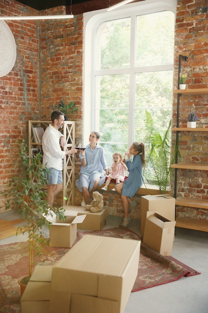 Nuova vita. la famiglia adulta si è trasferita in una nuova casa o appartamento. i coniugi ei figli sembrano felici e fiduciosi Foto Gratuite