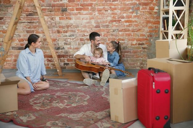 Новая жизнь. взрослая семья переехала в новый дом или квартиру. супруги и дети выглядят счастливыми и уверенными. переезд, отношения, концепция образа жизни. распаковываем коробки со своими вещами, вместе играем. Бесплатные Фотографии