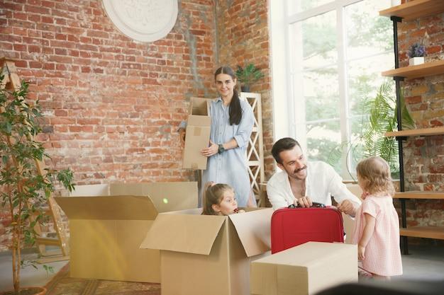 Новая жизнь. взрослая семья переехала в новый дом или квартиру. супруги и дети выглядят счастливыми и уверенными. переезд, отношения, новая концепция жизни. распаковываем коробки со своими вещами, вместе играем. Бесплатные Фотографии