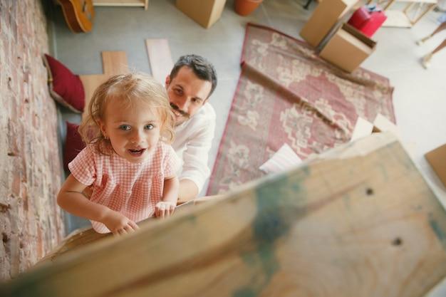 Новая жизнь. молодой отец с дочерью переехали в новый дом или квартиру. выглядите счастливым и уверенным. переезд, отношения, концепция образа жизни. вместе играем, готовимся к ремонту и смеемся. Бесплатные Фотографии